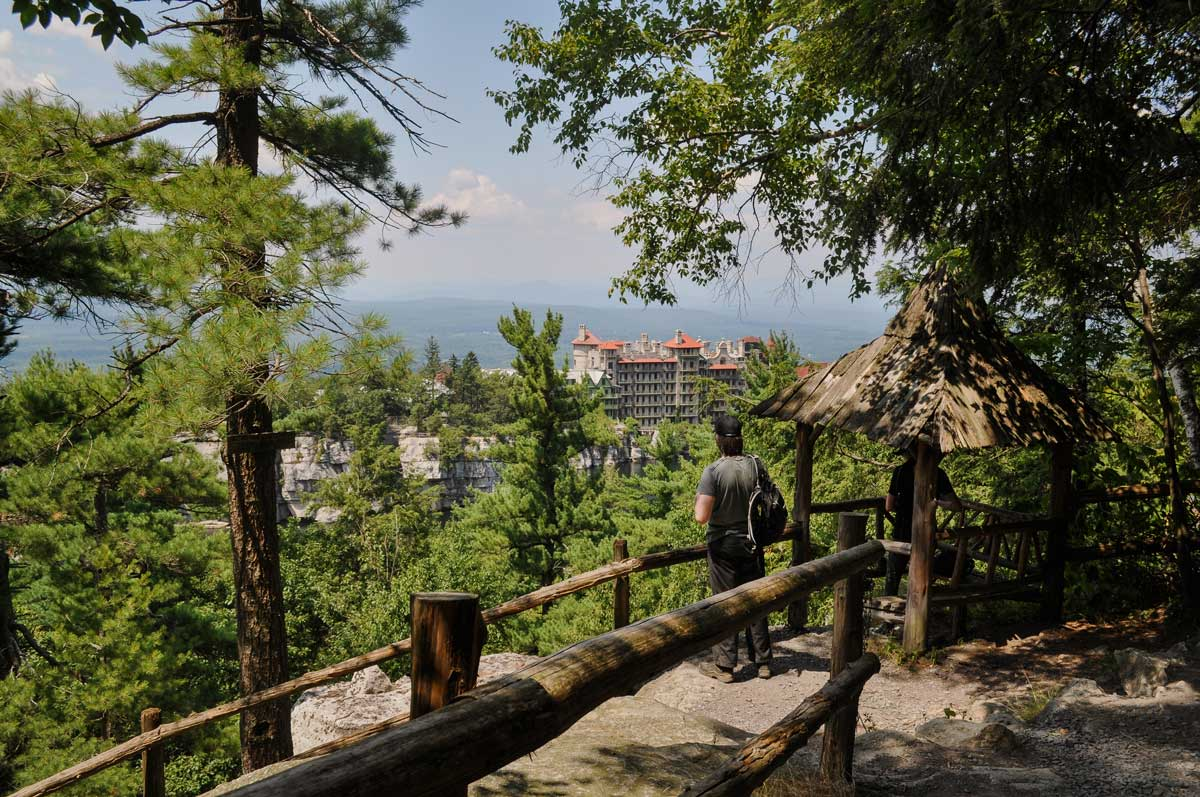 person standing in woods looking at mohonk mountainhouse