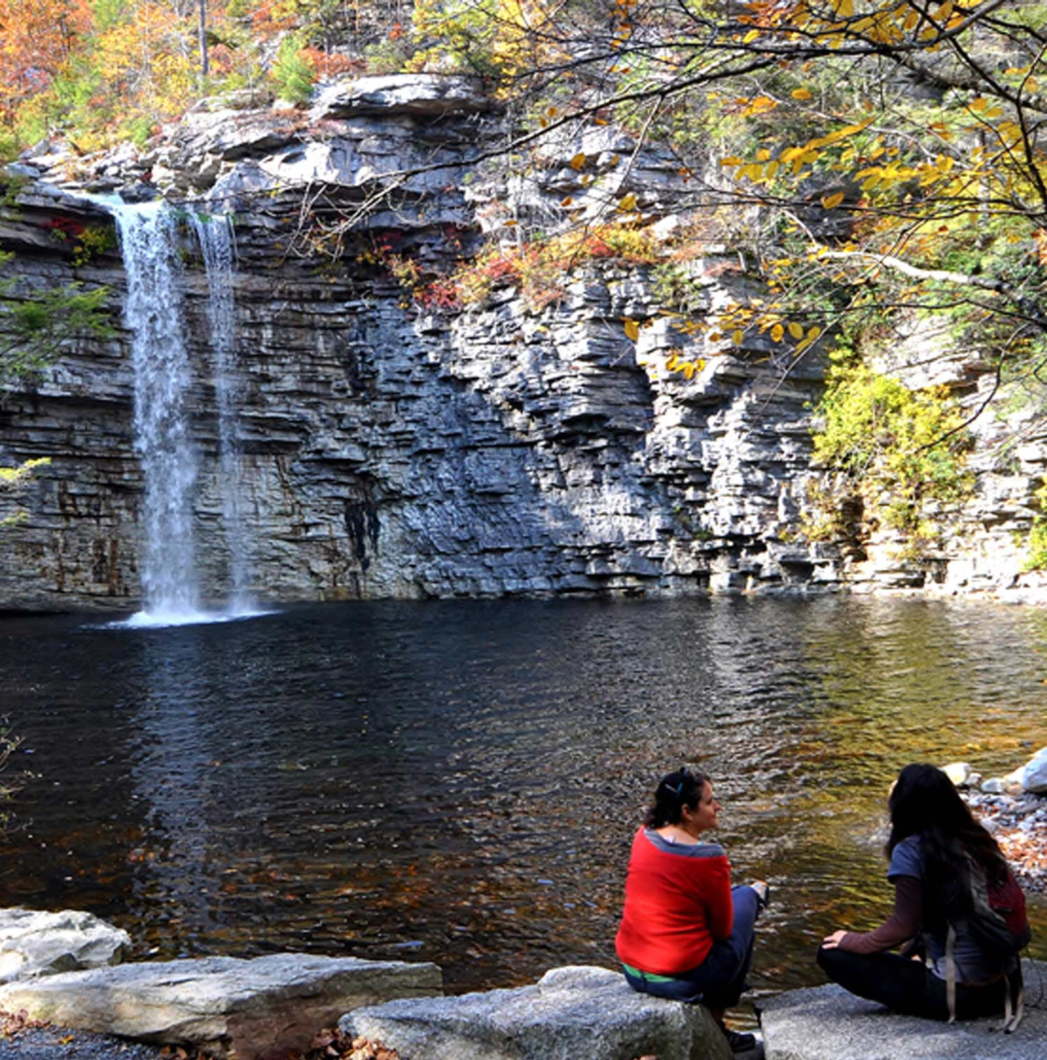 two people sitting at a waterfalls edge in gardiner